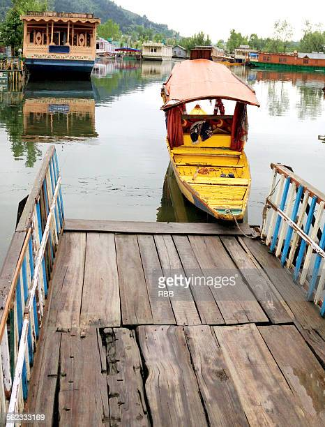 a shikara boat anchored outside house boat - kashmir valley stock photos and pictures