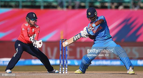 Shikha Pandey of India hits the ball towards the boundary as Sarah Taylor of England looks on during the Women's ICC World Twenty20 India 2016 match...