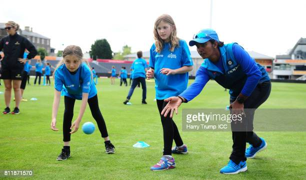 Shikha Pandey of India takes part in a catching activity alongside school children during the Cricket for Good India event at The County Ground on...