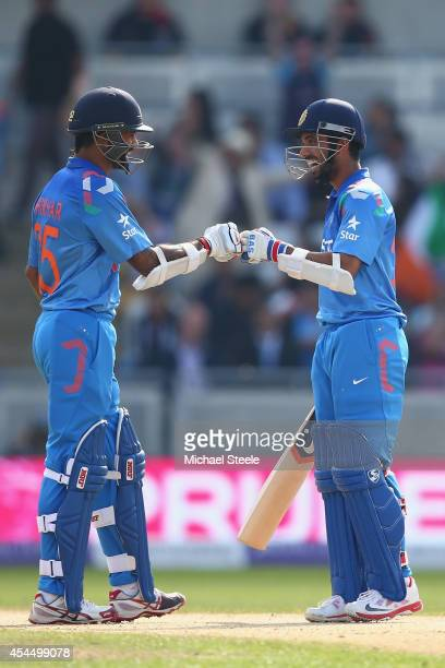 Shikhar Dhawan is congratulated by Ajinkya Rahane of India after hitting a six off the bowling of James Anderson during the fourth Royal London...