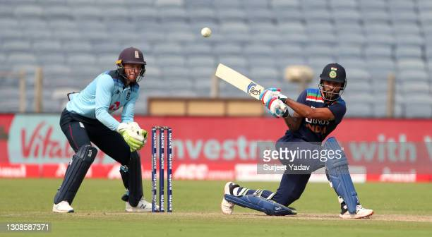 Shikhar Dhawan of India bats watched by England wicketkeeper Jos Buttler during 1st One Day International between India and England at MCA Stadium on...