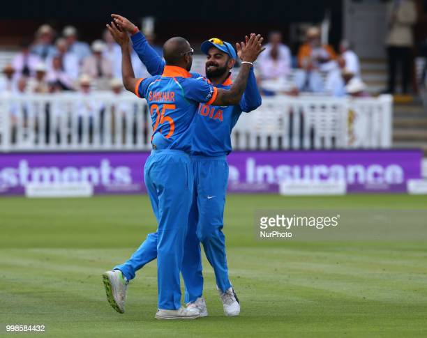 Shikhar Dhawan of India celebrates with Virat Kohli of India after his catch of England's Eoin Morgan during 2nd Royal London One Day International...