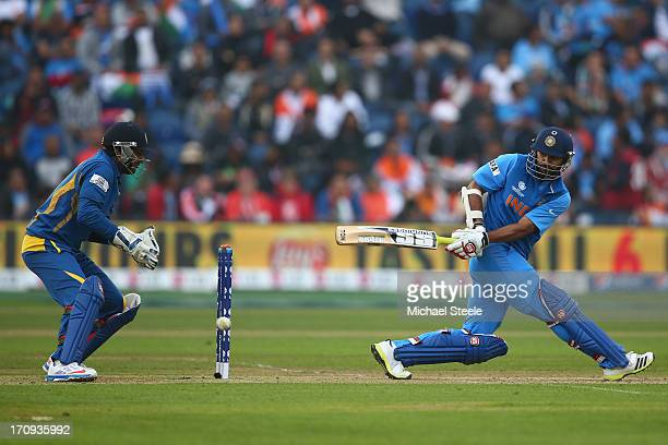Shikhar Dhawan of India sweeps a delivery as wicketkeeper Kumar Sangakkara of Sri Lanka looks on during the ICC Champions Trophy SemiFinal match...