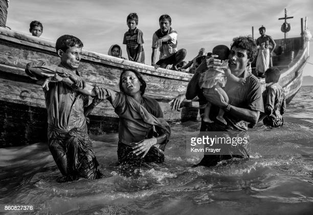 COX'S BAZAR BANGLADESH OCTOBER 01 A Rohingya refugee woman is helped from a boat as she arrives exhausted on the Bangladesh side of the Naf River at...