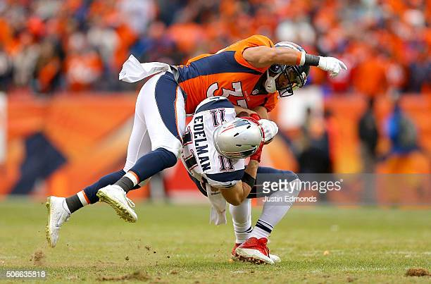 Shiloh Keo of the Denver Broncos tackles Julian Edelman of the New England Patriots in the fourth quarter in the AFC Championship game at Sports...
