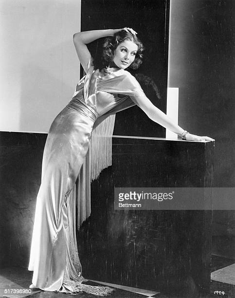 Shimmering white satin forms effective draping for Loretta Young MGM player who is smartly attired for the evening affair