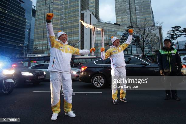 Shin Dongbin chairman of Lotte Group holds the PyeongChang 2018 Winter Olympics torch in front of the Lotte World Tower during the PyeongChang 2018...