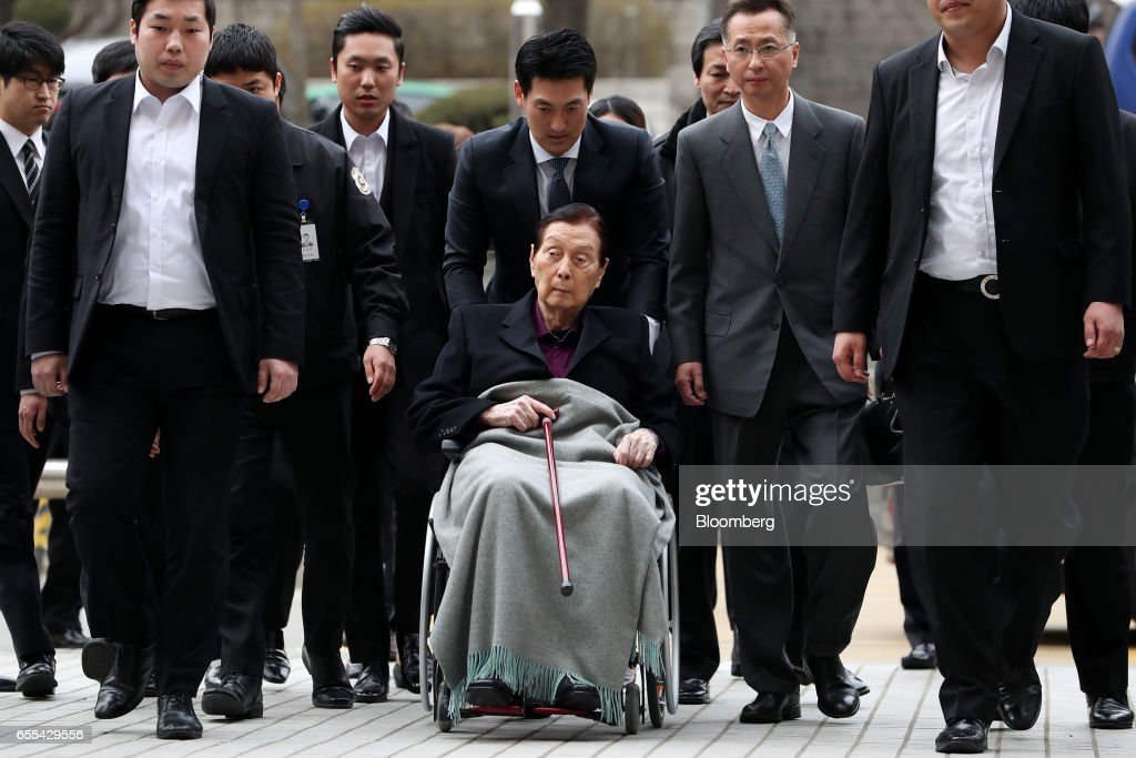 Shin Kyuk-ho, founder and honorary chairman of Lotte Group, center, sits in a wheelchair as he arrives at the Seoul Central District Court in Seoul, South Korea, on Monday, March 20, 2017. The Shin family trial began the proceeding today after indicting Lotte Group founder Shin Kyuk-ho and his three oldest children in October on charges ranging from embezzlement to fiduciary breaches amounting to about 280 billion won ($247 million). Photographer: SeongJoon Cho/Bloomberg via Getty Images