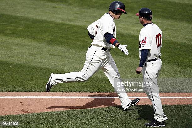 Shin Soo Choo of the Cleveland Indians is congratulated by third base coach Steve Smith after he hit a home run in the first inning against the Texas...