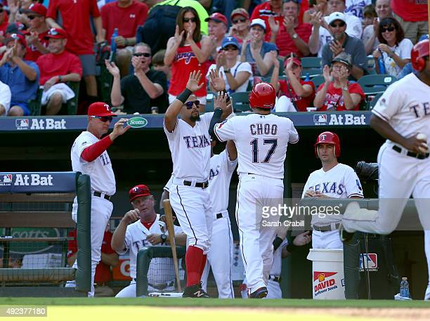 Shin Soo Choo of the Texas Rangers is congratulated by teammates in the dugout after scoring on a wild pitch in the bottom of the third inning of...