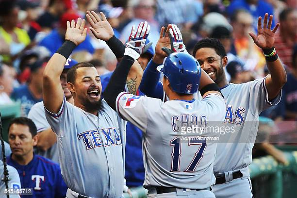 Shin Soo Choo of the Texas Rangers returns to the dugout after hitting a home run in the first inning during the game against the Boston Red Sox at...