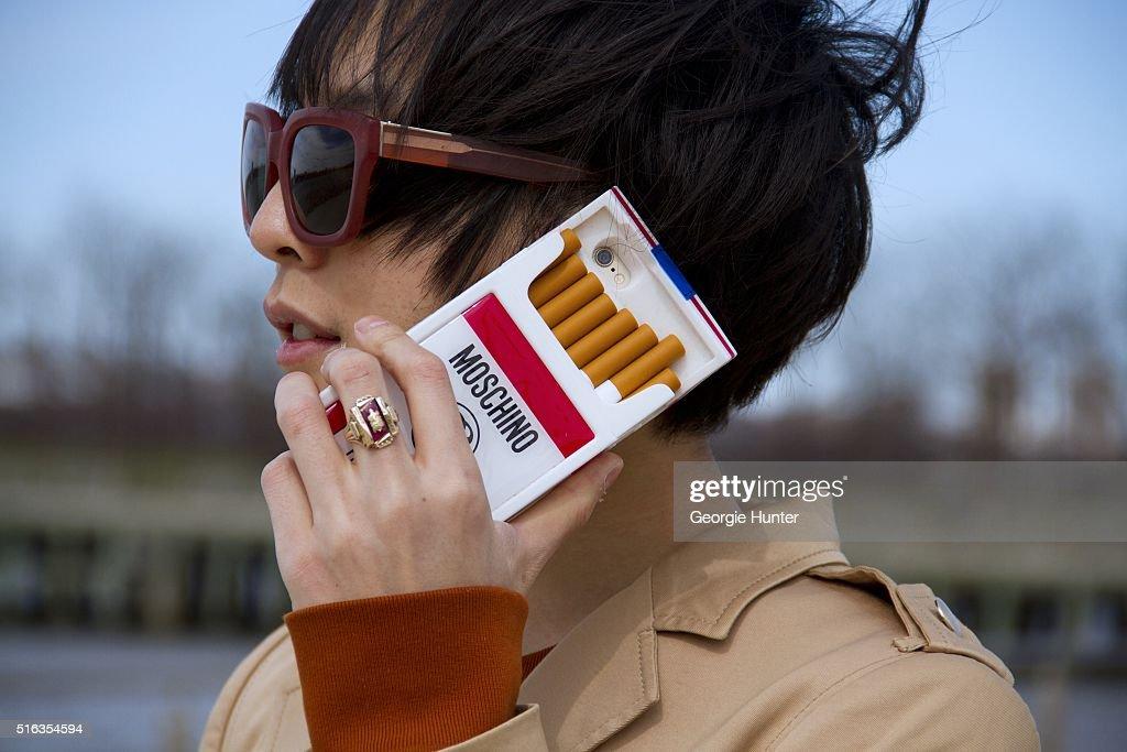 Shin Yamada wearing khaki jacket by Gucci, orange sweater by 3.1 Phillip Lim, Moschino 'Fashion Kills' cigarette iPhone case, red 3.1 Phillip Lim sunglasses and Delfina Delettrez ring March 18, 2016 in New York City.
