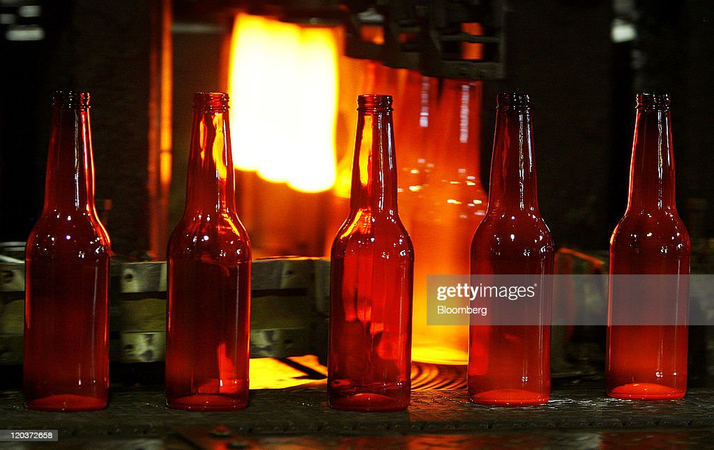 Shiner Beer bottles exit a forming machine at the Owens-Illinois Inc. glass manufacturing plant in Waco, Texas, U.S., on Thursday, Aug. 4, 2011. Owens-Illinois Inc., the world's largest glass container manufacturer, delivers safe, effective and sustainable glass packaging solutions to a growing global marketplace. Photographer: Mike Fuentes/Bloomberg via Getty Images