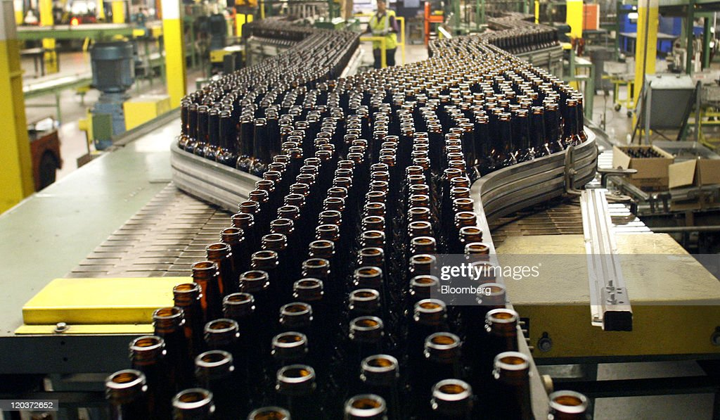 Shiner Beer bottles move down a conveyor belt at the Owens-Illinois Inc. glass manufacturing plant in Waco, Texas, U.S., on Thursday, Aug. 4, 2011. Owens-Illinois Inc., the world's largest glass container manufacturer, delivers safe, effective and sustainable glass packaging solutions to a growing global marketplace. Photographer: Mike Fuentes/Bloomberg via Getty Images