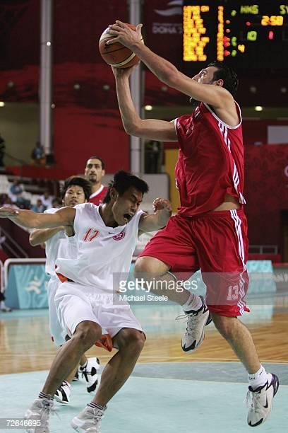 Shing Yee Fong of Hong KongChina feele the force of Salah Shawa of Syria during the 15th Asian Games Doha 2006 Men's Group C 1st Round Basketball...