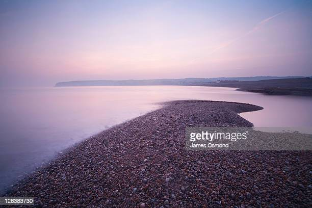 Shingle Bank at the mouth of the River Axe, Seaton Bay. Devon. England. UK.