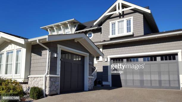 shingle style home with double and single car garages - eaves stock photos and pictures