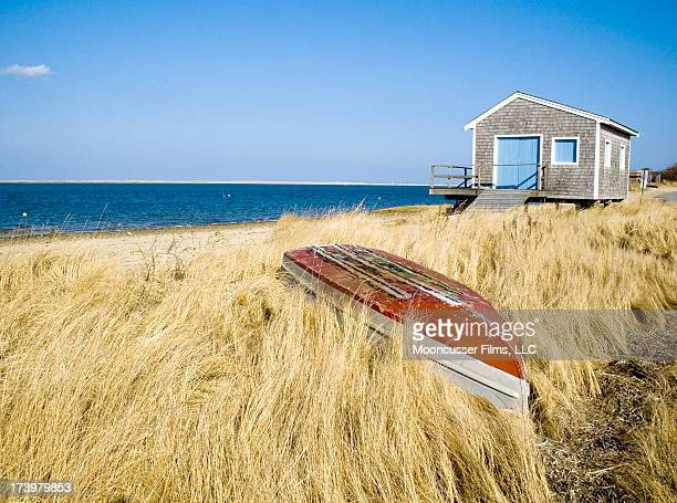 Shingled cottage with blue doors sits atop a beach and golden marsh on Pleasant Bay at Chatham, Cape Cod.