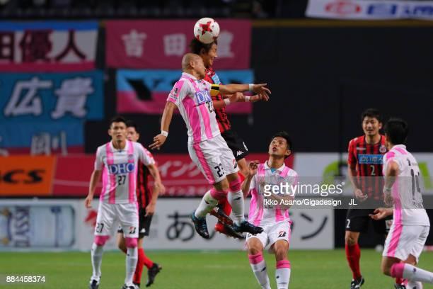 Shingo Hyodo of Consadole Sapporo and Yutaka Yoshida of Sagan Tosu compete for the ball during the JLeague J1 match between Consadole Sapporo and...