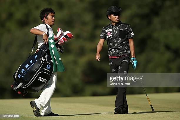 Shingo Katayama of Japan and caddie react after his second shot on the 15th hole during day three of the Panasonic Japan Open at Ibaraki Golf Club on...