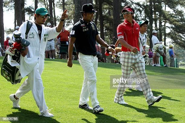 Shingo Katayama of Japan and Ryo Ishikawa of Japan walk with their caddies Masaki Tani and Hiroyuki Kato during a practice round prior to the 2010...