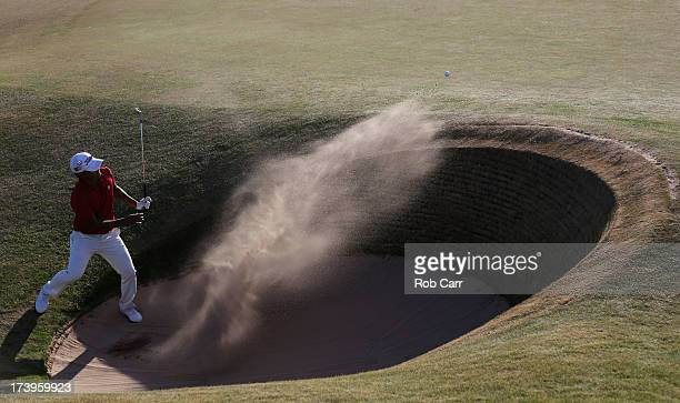 Shingo Katayama of Japan hits out of the bunker on the 13th hole during the first round of the 142nd Open Championship at Muirfield on July 18 2013...