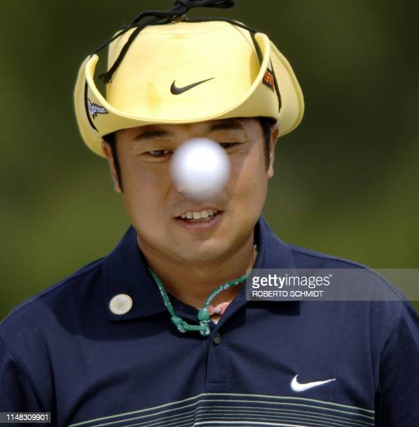 Shingo Katayama of Japan tosses a golf ball onto the green 06 April 2005 during the third practice round for the 2005 Masters Golf Tournament at the...
