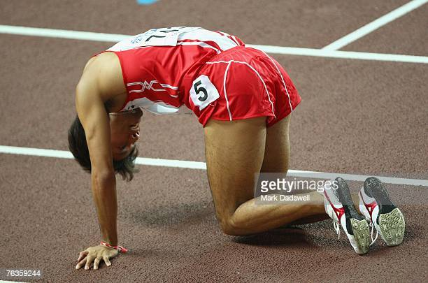 Shingo Suetsugu of Japan kneels exhausted after competing during the Men's 200m Quarter Finals on day four of the 11th IAAF World Athletics...