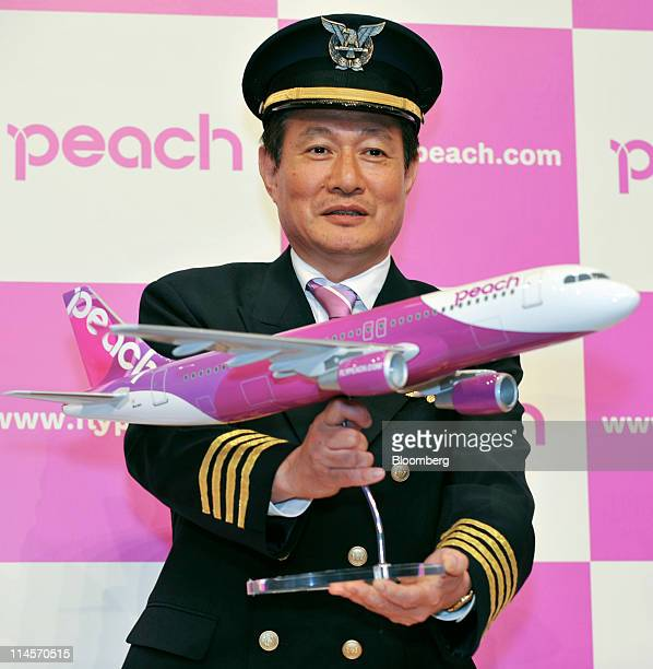 Shinichi Inoue chief executive officer of AF Aviation Co poses with a model of an airplane during a news conference unveiling the company's logo and...