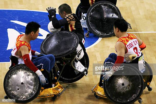 Shinichi Shimakawa of Japan is tackled by Tao Zhenfeng and Cheng Shuangmiao of China during the 7/8 classification match of the Mixed Wheelchair...
