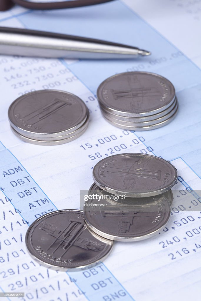 Shining coins in transaction book : Stock Photo