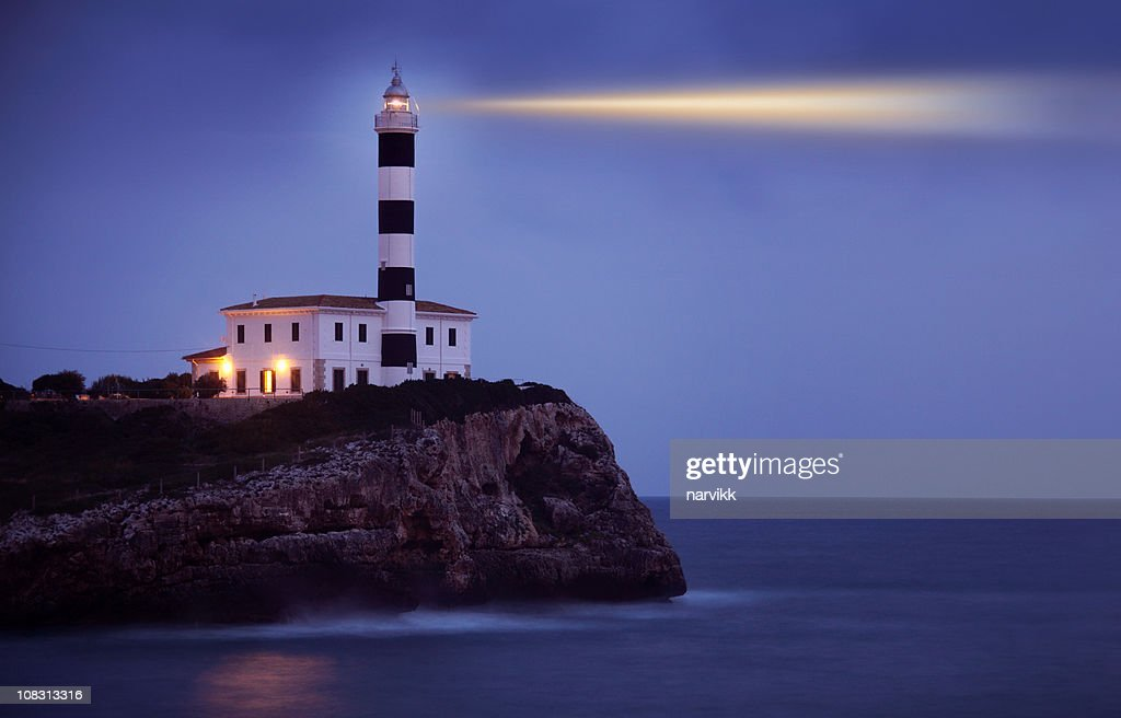 Shining Lighthouse on the Cliff by Night : Stock Photo