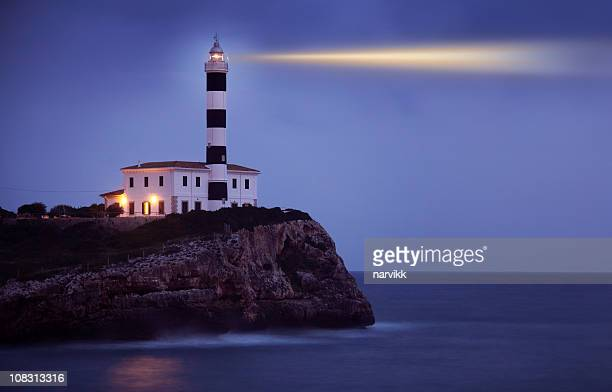 Shining Lighthouse on the Cliff by Night