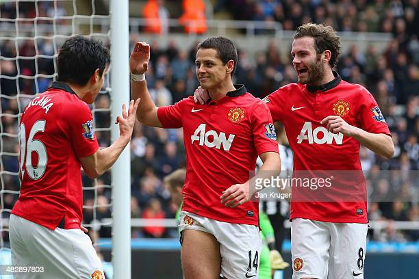 Shinji Kagawa and Juan Mata of Manchester United congratulate Javier Hernandez of Manchester United on scoring their third goal during the Barclays...