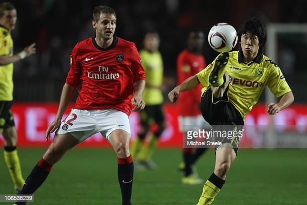 Shinji Kagawa of Borussia controls the ball as Mathieu Bodmer looks on during the UEFA Europa League Group J match between Paris Saint Germain and...