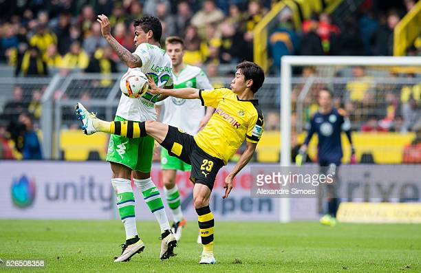 Shinji Kagawa of Borussia Dortmund challenges Luiz Gustavo of VfL Wolfsburg during the Bundesliga match between Borussia Dortmund and VfL Wolfsburg...