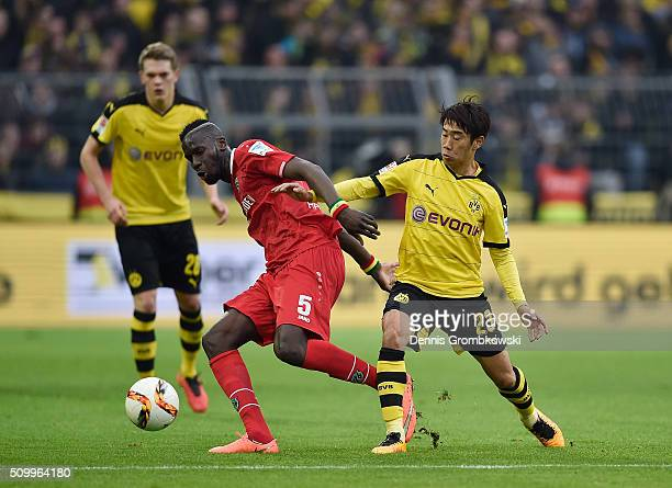 Shinji Kagawa of Borussia Dortmund challenges Salif Sane of Hannover 96 during the Bundesliga match between Borussia Dortmund and Hannover 96 at...