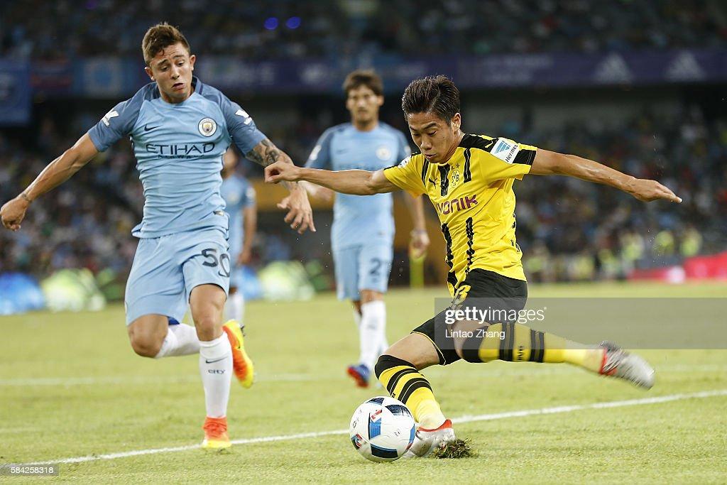 Shinji Kagawa of Borussia Dortmund contests the ball against Pablo Maffeo during the 2016 International Champions Cup match between Manchester City and Borussia Dortmund at Shenzhen Universiade Stadium on July 28, 2016 in Shenzhen, China.