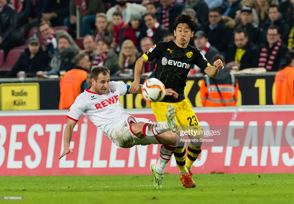 Shinji Kagawa of Borussia Dortmund gets challenged by Matthias Lehmann of Koln during the Bundesliga match between 1. FC Koeln and Borussia Dortmund at RheinEnergieStadion on December 19, 2015 in Cologne, Germany.