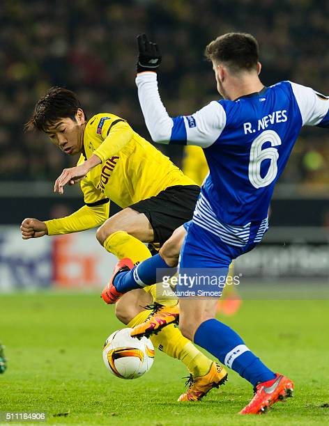 Shinji Kagawa of Borussia Dortmund gets challenged by Ruben Neves of FC Porto during the UEFA Europa League Round of 32 First Leg match between...