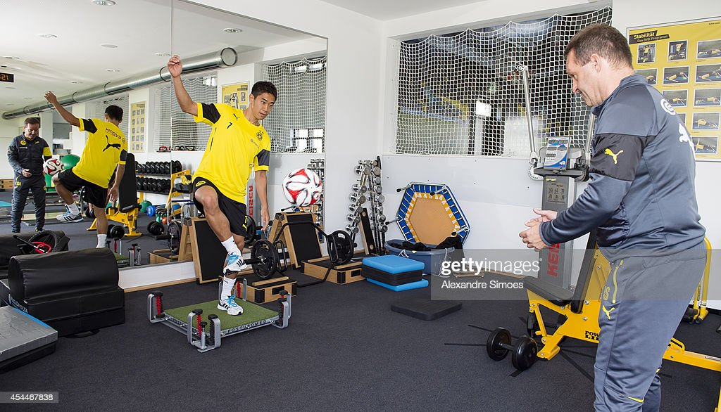 Shinji Kagawa of Borussia Dortmund in action with Athletic Coach Dr. Andreas Schlumberger during his first training session for the club on September 01, 2014 in Dortmund, Germany.