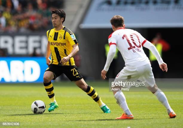 Shinji Kagawa of Borussia Dortmund is challenged by Daniel Baier of Augsburg during the Bundesliga match between FC Augsburg and Borussia Dortmund at...