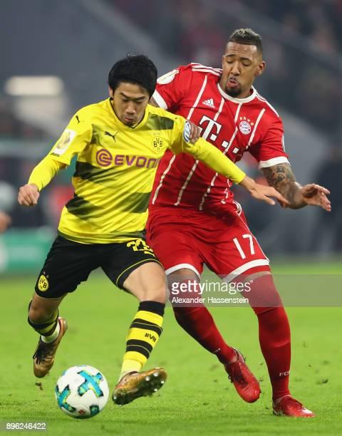Shinji Kagawa of Borussia Dortmund is challenged by Jerome Boateng of Bayern Muenchen during the DFB Cup match between Bayern Muenchen and Borussia...