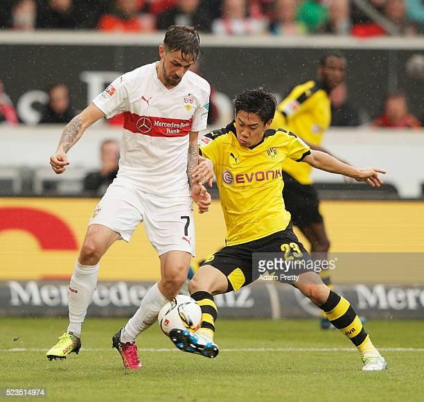 Shinji Kagawa of Borussia Dortmund is challenged by Martin Harnik of VfB Stuttgartl during the Bundesliga match between VfB Stuttgart and Borussia...