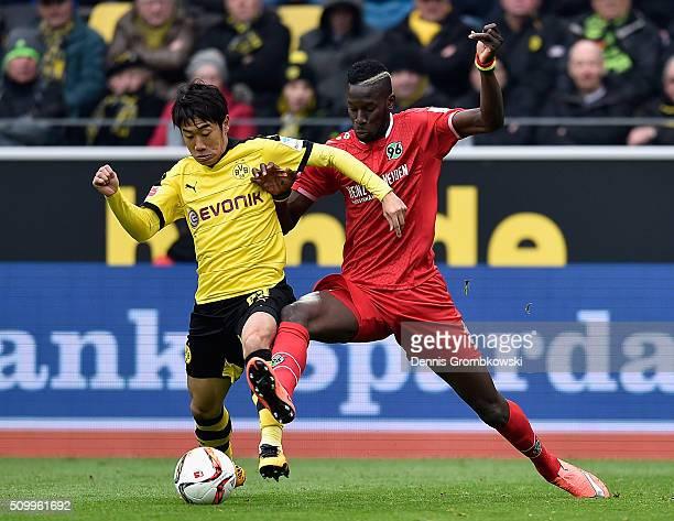 Shinji Kagawa of Borussia Dortmund is challenged by Salif Sane of Hannover 96 during the Bundesliga match between Borussia Dortmund and Hannover 96...