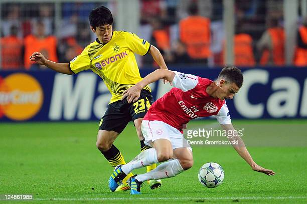 Shinji Kagawa of Dortmund and Laurent Koscielny of Arsenal battle for the ball during the UEFA Champions League Group F match between Borussia...