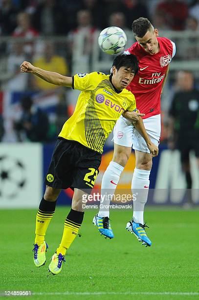 Shinji Kagawa of Dortmund and Laurent Koscielny of Arsenal jump for a header during the UEFA Champions League Group F match between Borussia Dortmund...