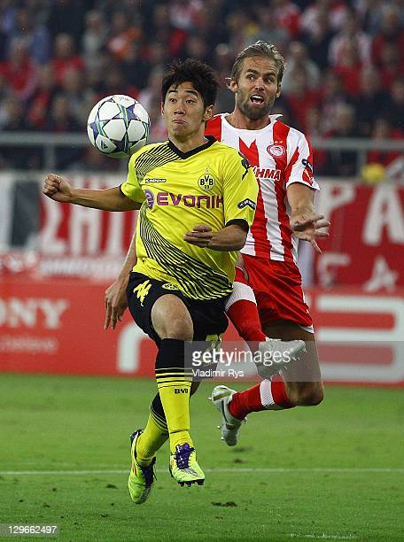 Shinji Kagawa of Dortmund attacks defended by Olof Mellberg of Olympiacos during the UEFA Champions League group F match between Olympiacos FC and...