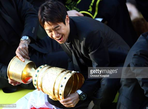 Shinji Kagawa of Dortmund catches the trophy during a parade at Borsigplatz celebrating Borussia Dortmund's Bundesliga and DFB Cup win on May 13 2012...