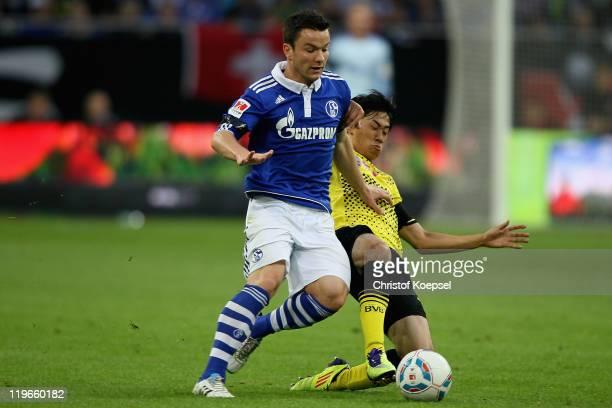 Shinji Kagawa of Dortmund challenchallenges Alexander Baumjohann of Schalke during the Supercup match between FC Schalke 04 and Borussia Dortmund at...